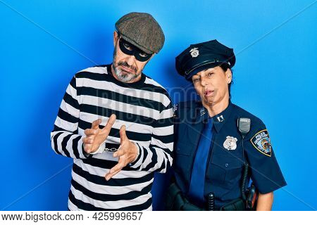 Middle age couple of hispanic woman and man wearing thief and police uniform looking sleepy and tired, exhausted for fatigue and hangover, lazy eyes in the morning.