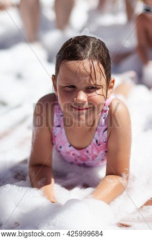 A Cute Girl In A Pink Swimsuit Lies Under The Foam At A Foam Party On The Beach By The Sea On Summer