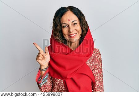 Middle age hispanic woman wearing tradition sherwani saree clothes with a big smile on face, pointing with hand and finger to the side looking at the camera.