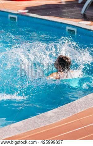 The Child Has Fun Jumping Into The Water From The Side Of The Pool And Sending Splashes Of Water Aro