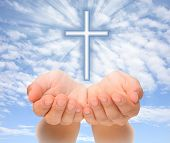 Hands holding Christian cross with light beams over sky poster