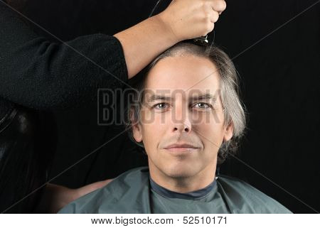 Close-up of a serious man looking to camera while his long hair is shaved off for a cancer fundraiser. poster