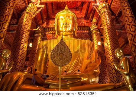 People work with cloth on Buddha image in Wat Phanan Choeng temple