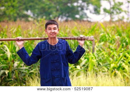 Teenager boy in thailand'ss agriculturist dress standing at corn field