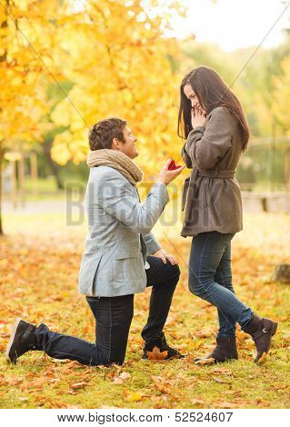 holidays, love, couple, relationship and dating concept - kneeled man proposing to a woman in the autumn park