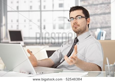 Young stock broker working in bright office, sitting at desk, using laptop, wearing glasses.