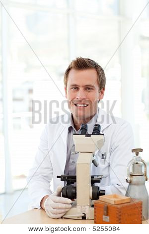 Male Scientist Looking At A Slide Under A Microscope
