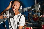 Young male singer in a recording studio poster