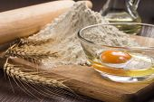 Baking ingredients with wheat ears on wood board poster