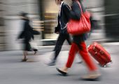 People with a red bag and a suitcase walking down the street. Intentional motion blur poster