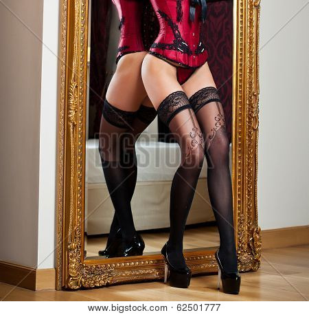 Attractive woman in red lingerie posing challenging near a large mirror. Sensual with long legs