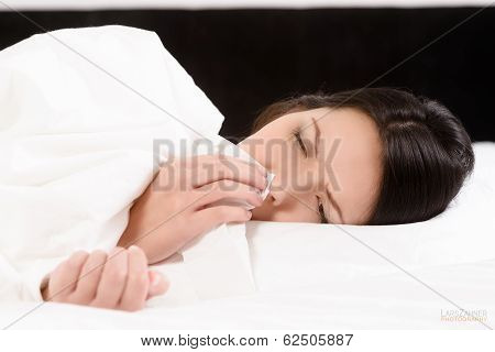 Sick Young Woman Blowing Her Nose On A Tissue
