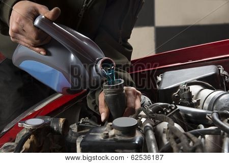 Car repairman pouring antifreeze into old engine