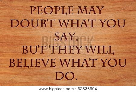 People may doubt what you say, but they will believe what you do - motivational quote by Lewis Cass on wooden red oak background poster