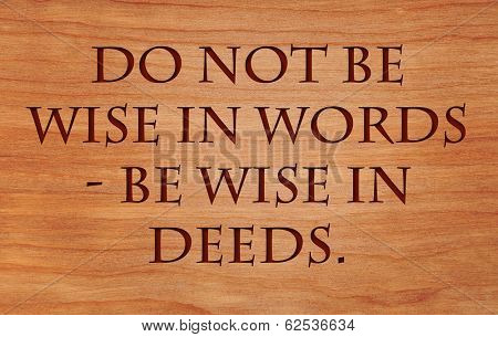 Do not be wise in words - be wise in deeds - motivational Jewish Proverb on wooden red oak background