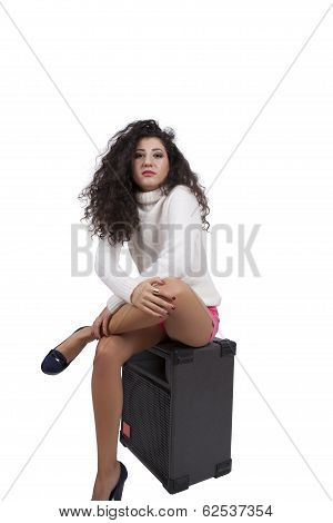 Seductive female fashion model posing on a speaker