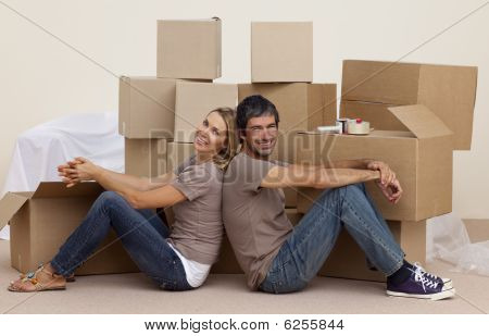 Smiling Couple Sitting On Floor Around Boxes
