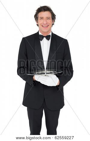 Portrait of happy waiter holding empty tray over white background