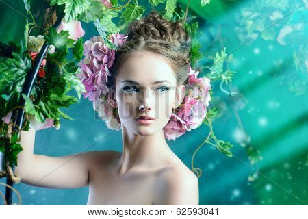 Beautiful young woman standing under an arch of flowers and overgrown loach. Magic of the spring.