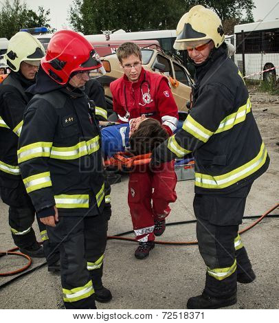 Firefighters And Rescuers Taking Away Injured On A Stretcher By The Car Accident