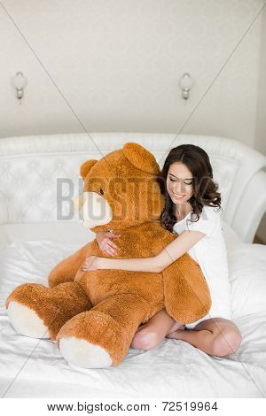 Pretty girl lying on the bed with a teddy bear