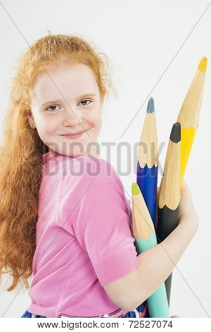Cute And Happy Red-haired Caucasain Girl Playing With Huge Pencils