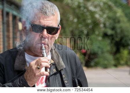 Man In Sunglasses Puffing On An E-cigarette