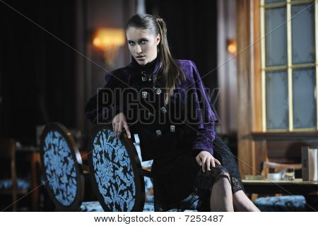 beautiful young woman lady in fashion dress posing in restaurant or bar at night poster