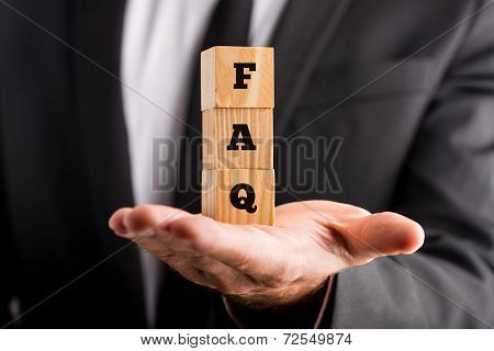 Businessman Holding Blocks Spelling Faq