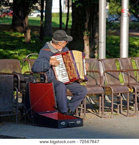 Accordion Player Sitting On Bench In City Park, Vienna, Austria.