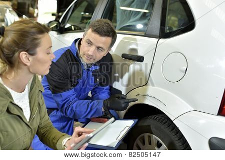 Mechanician with insurance adjuster checking on auto repair poster