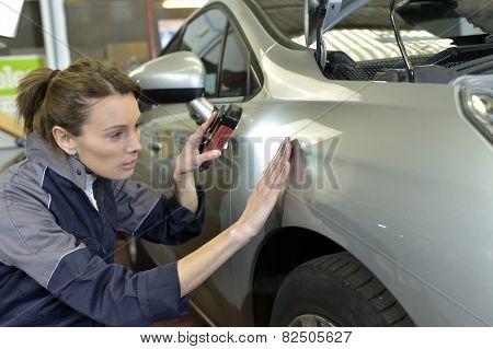 Woman technician working in auto bodywork shop