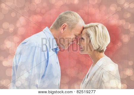 Happy mature couple facing each other against light glowing dots design pattern