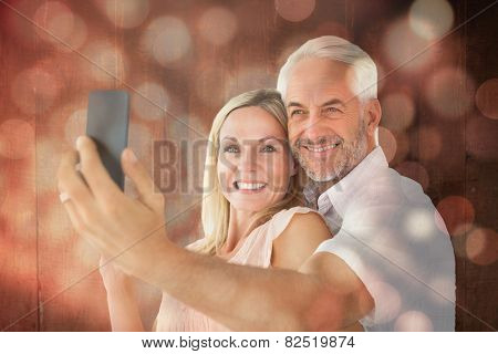 Happy couple posing for a selfie against light circles on black background