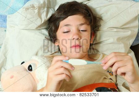 Sick Preteen Boy In Bed With Termometer Show High Temperature