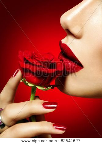 Beautiful Model woman kissing red rose flower. Red Lips, Nails and Rose. Beauty Girl. Makeup and Manicure. Sensual Mouth. Sexy Red Color Lips. St. Valentine's Day design. Part of Face