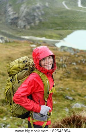 Hiker woman hiking with backpack in rain on trek living healthy active lifestyle. Smiling cheerful girl walking on hike in beautiful mountain nature landscape while raining in Swiss alps, Switzerland.