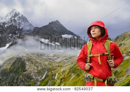 Alps Hiking - Asian hiker woman in Switzerland on trek in mountains with backpack living a healthy active lifestyle. Hiker girl on nature landscape hike in Urner Alps, Berne, Swiss alps, Switzerland. poster