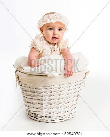 cute little girl in a wicker basket with lace headband