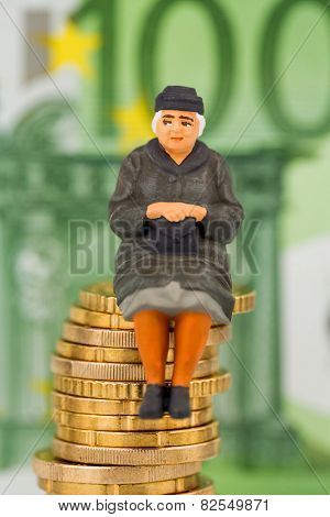 pensioner sitting on money stack symbol photo for pension, retirement, old age