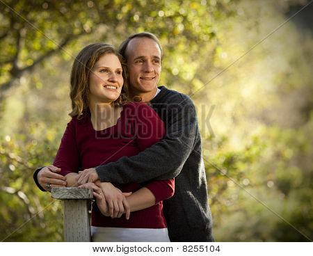 Couple hugging on wooden bridge