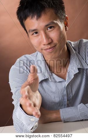 Successful business man of Chinese sitting and want to shake hand with you, closeup portrait in studio.