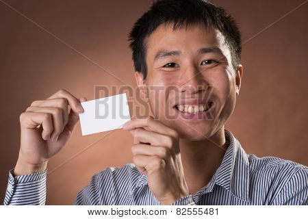 Young Chinese frank businessman holding blank white business card, closeup portrait in studio.