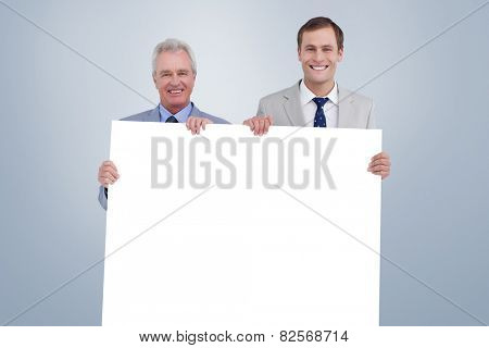 Smiling tradesmen holding blank sign against grey vignette