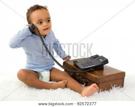 Adorable little 18 month old toddler boy of African decent playing with a telephone