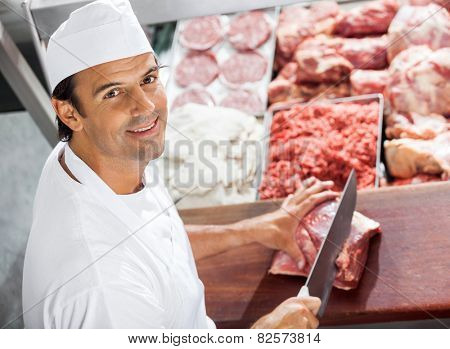 High angle portrait of confident butcher cutting meat at counter in butchery poster