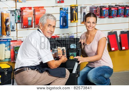 Portrait of senior salesman showing tool to female customer in hardware store