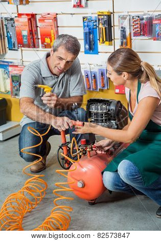 Saleswoman showing air compressor to male customer in hardware store