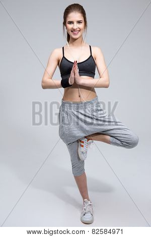 Happy sports woman doing yoga excersises over gray background