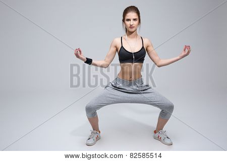Beautiful fit woman doing excersises over gray background